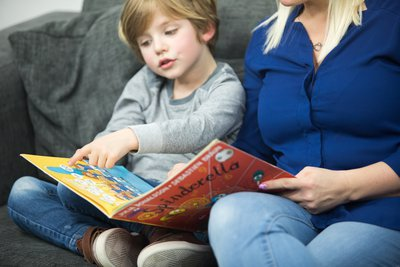 boy pointing to book with mum